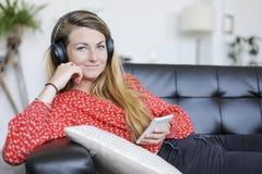 Mujer feliz que escucha los auriculares que llevan de la música que miran la leva Imágenes de archivo libres de regalías