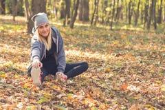 Mujer feliz que estira antes de correr en el bosque imagen de archivo