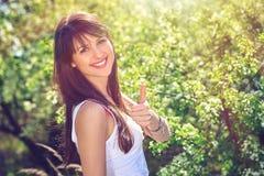 Mujer feliz que gesticula el pulgar para arriba al aire libre Fotos de archivo