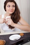Mujer feliz que goza de té y de las galletas Foto de archivo libre de regalías