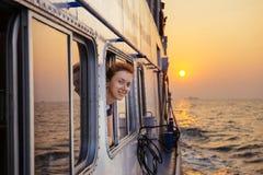 Mujer feliz que goza del mar del transbordador en puesta del sol imagenes de archivo