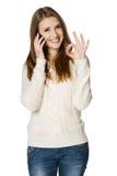 Mujer feliz que habla en el teléfono celular y que muestra OK Foto de archivo libre de regalías