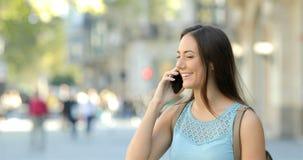 Mujer feliz que habla en el teléfono en la calle