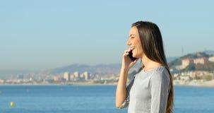 Mujer feliz que habla en el teléfono en la playa