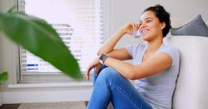 Mujer feliz que habla en el teléfono móvil en la sala de estar 4k almacen de metraje de vídeo