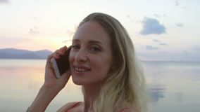 Mujer feliz que habla en el teléfono, riendo en la playa almacen de video