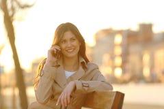 Mujer feliz que habla en el teléfono que se sienta en la puesta del sol foto de archivo libre de regalías