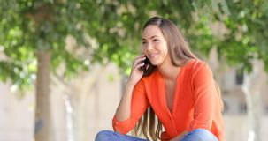 Mujer feliz que habla en el teléfono que se sienta en un parque