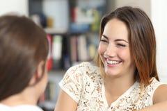 Mujer feliz que habla y que ríe con un amigo en casa Foto de archivo libre de regalías
