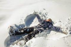 Mujer feliz que hace ángel de la nieve en la nieve fotografía de archivo
