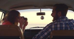 Mujer feliz que hace clic la foto del hombre con la c?mara digital 4k almacen de video