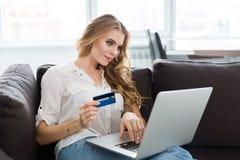 Mujer feliz que hace compras en Internet usando tarjeta de crédito Fotos de archivo libres de regalías
