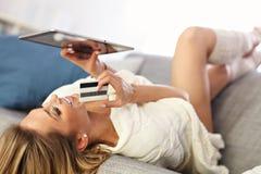 Mujer feliz que hace compras en línea con la tarjeta de crédito imagenes de archivo
