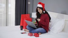 Mujer feliz que hace compras en línea para el regalo de la Navidad con el ordenador portátil del ordenador y la tarjeta de crédit
