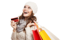 Mujer feliz que hace compras que sostiene bolsos y la tarjeta de crédito Ventas del invierno Foto de archivo
