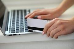 Mujer feliz que hace hacer compras en línea en casa Ciérrese para arriba de una mano que sostiene una tarjeta de crédito al lado  Fotos de archivo libres de regalías