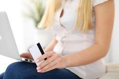 Mujer feliz que hace hacer compras en línea en casa Ciérrese para arriba de una mano que sostiene una tarjeta de crédito al lado  Imagen de archivo libre de regalías