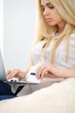 Mujer feliz que hace hacer compras en línea en casa Ciérrese para arriba de una mano que sostiene una tarjeta de crédito al lado  Imagenes de archivo