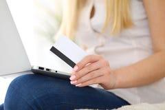 Mujer feliz que hace hacer compras en línea en casa Ciérrese para arriba de una mano que sostiene una tarjeta de crédito al lado  Foto de archivo libre de regalías
