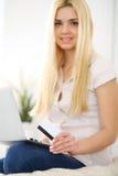 Mujer feliz que hace hacer compras en línea en casa Ciérrese para arriba de una mano que sostiene una tarjeta de crédito al lado  Fotografía de archivo