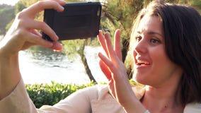 Mujer feliz que hace la llamada de teléfono video del lago en parque en vacaciones en primer del país europeo almacen de video