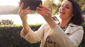 Mujer feliz que hace teléfono la llamada video delante del lago almacen de video