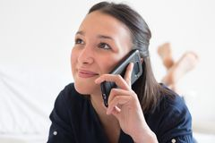 Mujer feliz que hace una llamada de teléfono en cama Fotos de archivo libres de regalías
