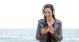Mujer feliz que hojea y que escucha la música