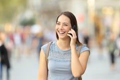 Mujer feliz que invita al teléfono en la calle Fotos de archivo