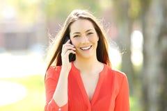 Mujer feliz que invita al teléfono que le mira Fotografía de archivo