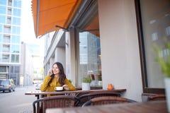 Mujer feliz que invita a smartphone en el café de la ciudad Imágenes de archivo libres de regalías
