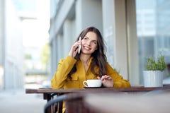 Mujer feliz que invita a smartphone en el café de la ciudad Fotografía de archivo libre de regalías