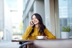 Mujer feliz que invita a smartphone en el café de la ciudad Imagen de archivo libre de regalías