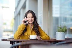 Mujer feliz que invita a smartphone en el café de la ciudad Imagen de archivo
