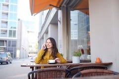 Mujer feliz que invita a smartphone en el café de la ciudad Fotos de archivo