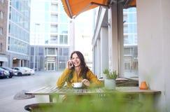 Mujer feliz que invita a smartphone en el café de la ciudad Imagenes de archivo