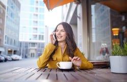 Mujer feliz que invita a smartphone en el café de la ciudad Foto de archivo libre de regalías