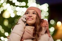 Mujer feliz que invita a smartphone en la Navidad Imagen de archivo libre de regalías
