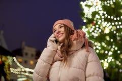 Mujer feliz que invita a smartphone en la Navidad Imagenes de archivo