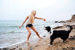 Mujer feliz que juega con el perro y que se divierte en la playa Imagen de archivo