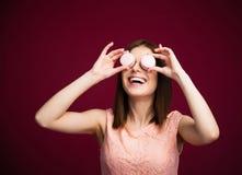 Mujer feliz que la cierra ojos con las galletas redondas Fotos de archivo