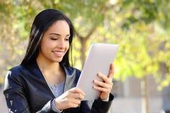 Mujer feliz que lee a un lector de la tableta en un parque Imagenes de archivo