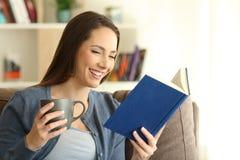 Mujer feliz que lee un libro de papel solamente en casa Imágenes de archivo libres de regalías