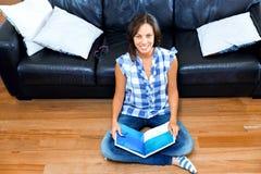 Mujer feliz que lee un libro en el piso Imagen de archivo libre de regalías