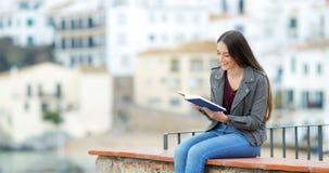 Mujer feliz que lee un libro en una repisa almacen de video