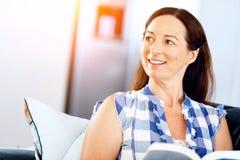 Mujer feliz que lee un libro que se relaja en un sofá Foto de archivo libre de regalías