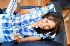 Mujer feliz que lee un libro que se relaja en un sofá Imágenes de archivo libres de regalías