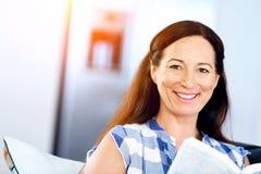 Mujer feliz que lee un libro que se relaja en un sofá Imagen de archivo libre de regalías