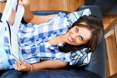 Mujer feliz que lee un libro que se relaja en un sofá Fotografía de archivo libre de regalías
