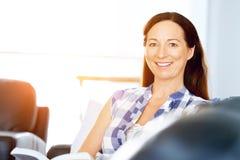 Mujer feliz que lee un libro que se relaja en un sofá Fotos de archivo